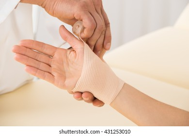 Close-up Of Doctor Hand Wrapping Elastic Bandage To Patient