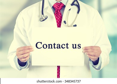 Closeup doctor hands holding white card sign with contact us text message isolated on hospital clinic office background. Retro instagram style filter image. Healthcare concept