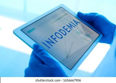 cierre de un médico, usando guantes quirúrgicos azules, con una tableta digital en las manos con la palabra infodemia, escrita en español, en su pantalla