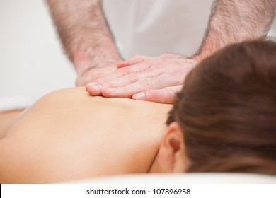 Close-up of a doctor massaging the back of a woman indoors