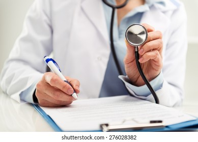Closeup of doctor physician reporting medical test results. Woman medic in uniform filling health insurance document in the office.  Shallow depth of field.