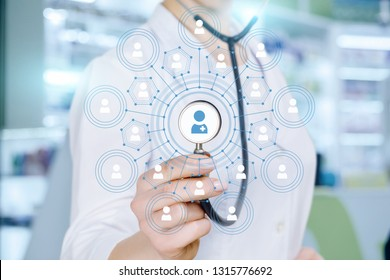 A closeup of a doctor touching the center of social medical service scheme structure with human figures fragments images inside with her stethoscope. The concept of public medical service.