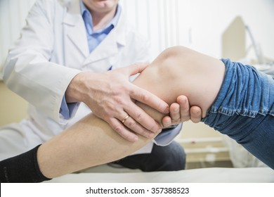 closeup doctor the traumatologist examines the patient the patient's ankle leg