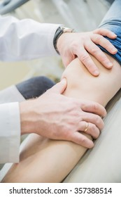 closeup doctor the traumatologist examines thepatient's knee and  leg