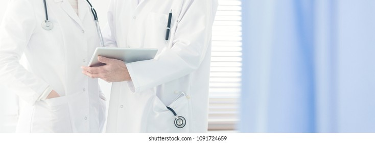 Close-up of a doctor in white coat with stethoscope holding a tablet, consulting on a case with a colleague in bright hospital