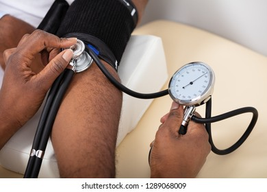 Close-up Of Doctor's Hand Measuring Blood Pressure Of Male Patient