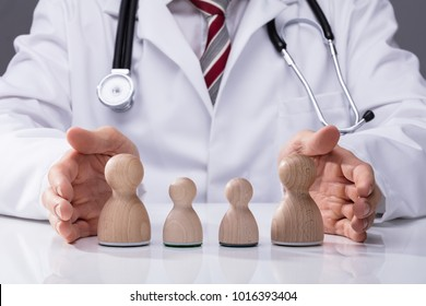 Close-up Of A Doctor's Hand Protecting Wooden Family On Desk