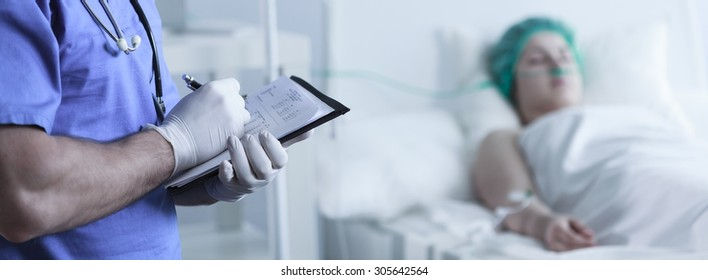 Close-up of doctor's hands filling in medical documents