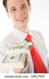 Close-up of dollar bills being given by man at background