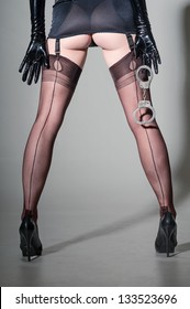Closeup of dominatrix in girdle & tan fully-fashioned seamed stockings, stilettoes, holding handcuffs
