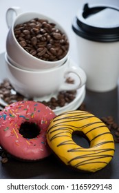 Close-up of donuts with coffee cups in the background, selective focus, vertical shot
