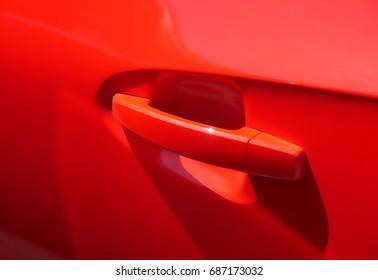 Closeup of door handle of a red modern car.