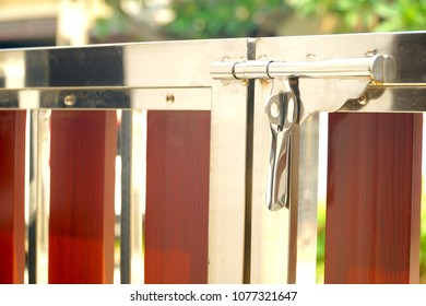 Close-up door lock of stainless steel and wooden gate. Modern style. Red and silver color. Protect your house. Copy space.