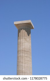 Close-up of a Doric column against a blue sky.