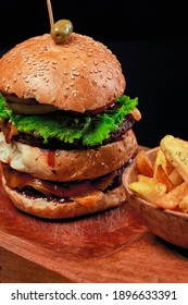 close-up of double burger with potatoes meat lettuce tomato and bread