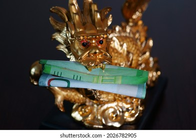 Close-up dragon figurine. In the dragon's teeth is a banknote. Symbol of well-being and monetary prosperity.