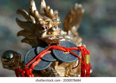 Close-up dragon figurine. In the dragon's teeth is a bunch of Chinese coins. Symbol of well-being and monetary prosperity.