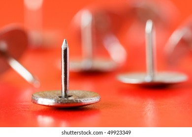close-up of  drawing pins  on red background