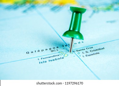 closeup of draw-pin stick into real map, travelling to Galapagos island, identification of final destination