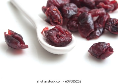 closeup of dried cranberries in a spoon on white background