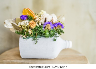 Close-up of dried flowers and fir tree branches potted in painted white bottle