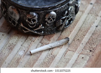 Closeup of dried marijuana and handmade joint cigarette. Suggestive ashtray along. Manually rolled weed joint for smoke.