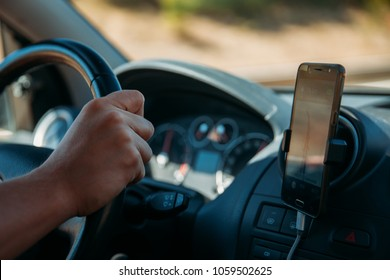 Closeup of driver using GPS from a smartphone while traveling.