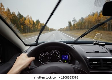 Close-up of driver's hands on car steering wheel. A man riding in the rain on the road. Work of windshield wipers - brushes