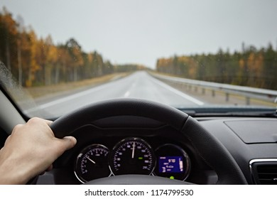 Close-up of driver's hands on car steering wheel. A man riding in the rain on the road.