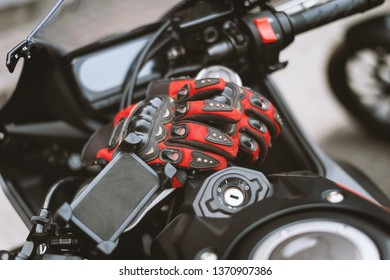 closeup driving gloves on bigbike with soft-focus and over light in the background