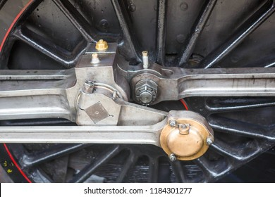 Close-up of the driving wheel and side rods of a vintage steam railway locomotive.