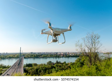Closeup of drone in the air, cityscape nature and bridge in background , beautiful sunny day