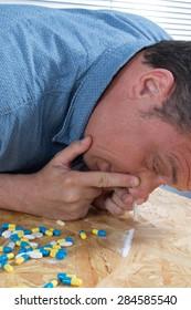 Close-up of drug addicted man taking cocaine