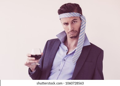 Closeup of drunk business man looking at camera, wearing tie on his head and holding glass of wine. Isolated view on white background.