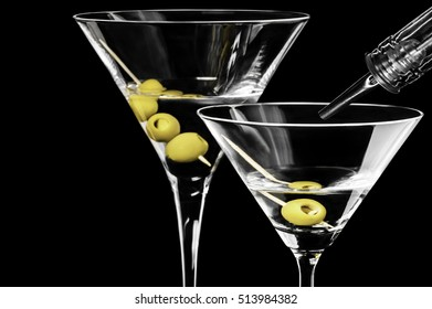Close-up of dry martini with green olives and a tube with dispenser on black background