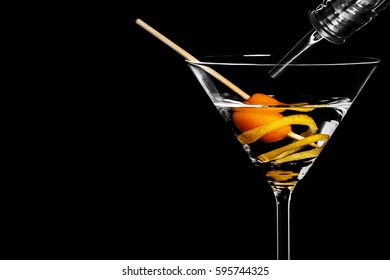 Close-up of dry martini with kumquat and lemon peel in the black background