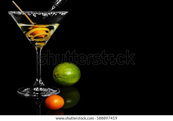 Close-up of dry martini with kumquats, lemon peel and lime in the black background