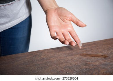 Close-up of dust on woman finger taken from wooden table