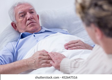 Close-up of a dying elderly man in a hospital bed, holding his wife's hand