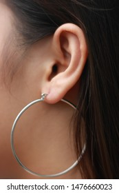 Close-up of the ears of a beautiful long-haired young Asian woman with her large circle earrings - image