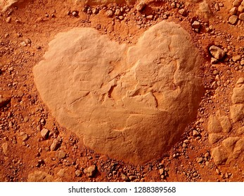 Closeup of an Earth Colored, Heart Shaped Rock on the Ground surrounded by Rusty, Red Soil as a Valentines Day Background
