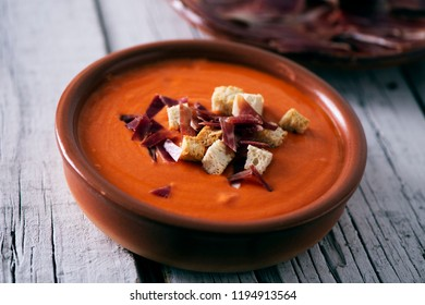 closeup of an earthenware bowl with spanish salmorejo cordobes or porra antequerana, a cold tomato soup, topped with serrano ham and croutons, on a white rustic table