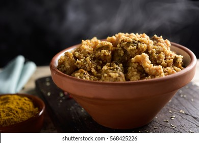 closeup of an earthenware casserole with couscous with chicken and vegetables on a rustic wooden table