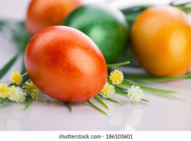 close-up easter orange egg end yellow small flowers on unfocused eggs and light background