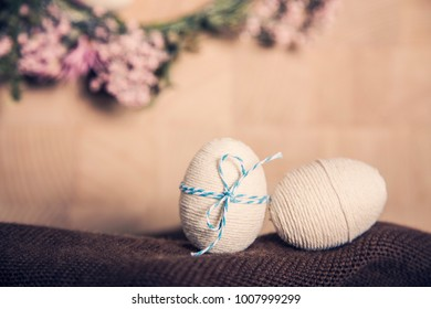 Closeup Easter still life background with Easter eggs and flower wreath, pastel colours decoration from rope, ribbon with wooden background