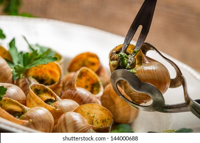 Closeup of eating the fried snails with garlic butter