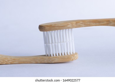 Closeup of eco-friendly bamboo wood toothbrushes isolated on white background