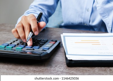 Closeup of economist using calculator. Person working with diagram at desk. Economy concept. Cropped view.