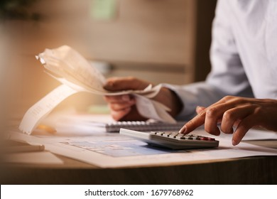 Close-up of economist using calculator while going through bills and taxes in the office.