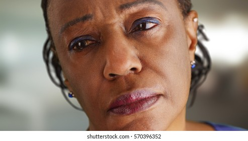 A close-up of a elderly black woman looking off in the distance sadly
